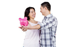 Happy couple looking at each other while holding piggy bank. Against white background stock image