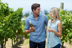 Happy couple looking at each other while holding wine bottle and glass Stock Images