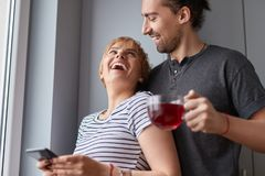 Happy couple looking at each other at home. Cheerful men with fresh tea and women with smartphone happily laughing and looking at each other while standing near royalty free stock photos