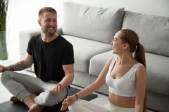 Happy couple looking at each other while meditating at home stock photography