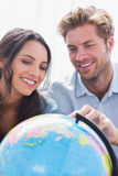 Happy couple looking at a globe Royalty Free Stock Photography