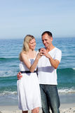 Happy couple looking at holiday photograph Royalty Free Stock Photography