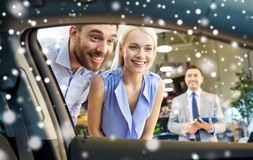 Happy couple looking inside car in auto show Royalty Free Stock Photos