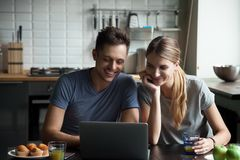 Happy couple looking at laptop screen together, laughing royalty free stock photos
