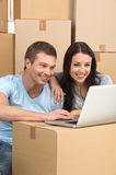 Happy couple looking at laptop sitting in new house. Royalty Free Stock Photo