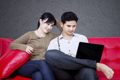 Happy couple looking at laptop on sofa Stock Image