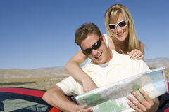 Happy Couple Looking At Map Stock Photo