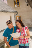 Happy couple looking at map in town. Travel vacation destination Royalty Free Stock Photo