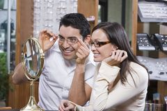 Happy Couple Looking At Mirror While Trying On Spectacles. Hispanic couple looking at mirror while trying on spectacles at shop Royalty Free Stock Image