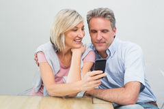 Happy couple looking at mobile phone Royalty Free Stock Photography