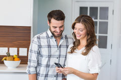Happy couple looking in mobile phone Stock Photo