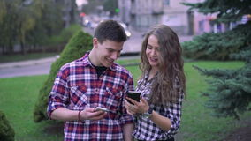 Happy couple looking on phones, laughing near trees in the center stock video