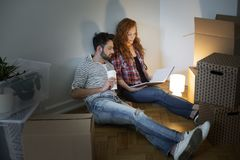 Happy couple looking at photo album while furnishing new home af. Ter relocation stock images