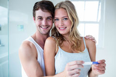 Happy couple looking at pregnancy test Stock Photos