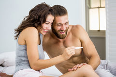 Happy couple looking at pregnancy test on bed Royalty Free Stock Photos