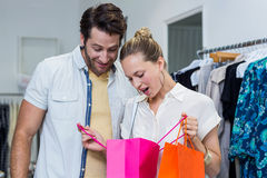Happy couple looking into shopping bags Stock Photography