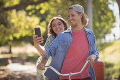 Happy couple looking at smart phone while riding bicycle. Against trees Stock Photography