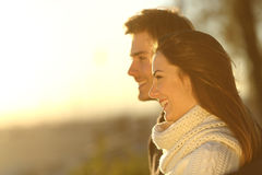 Happy couple looking at sunset in winter Stock Photos