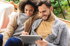 Happy couple looking into a tablet Stock Images