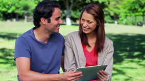 Happy couple looking at a tablet computer stock video
