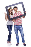 Happy couple looking through tablet frame Stock Photos