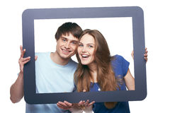 Happy couple looking through tablet frame Royalty Free Stock Photos
