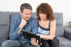 Happy couple looking at the tablet Stock Images