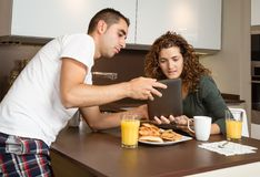 Happy couple looking tablet at home breakfast Stock Image