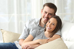 Happy couple looking to camera at home. Happy couple sitting in a comfortable couch in the living room and looking at you at home Stock Image