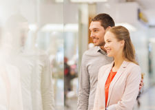 Happy couple looking to shop window in mall Royalty Free Stock Photography