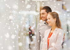 Happy couple looking to shop window in mall. Sale, consumerism and people concept - happy young couple looking to shop window in mall with snow effect Royalty Free Stock Image
