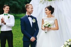 Happy couple looks at each other during the ceremony in garden.  royalty free stock image