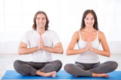 Happy couple in lotus pose Royalty Free Stock Photography