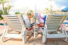 Happy couple in loungers by the pool by the sea. Nice happy couple in loungers by the pool by the sea royalty free stock images