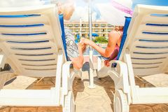 Happy couple in loungers by the pool by the sea. Nice happy couple in loungers by the pool by the sea stock photo