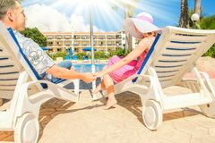 Happy couple in loungers by the pool by the sea. Nice happy couple in loungers by the pool by the sea royalty free stock image