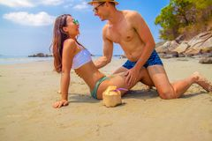 Happy couple in love on beach summer vacations. Joyful Asian girl piggybacking on young Caucasian boyfriend playing and having fun in sunny tropical royalty free stock images