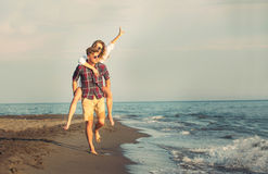 Happy couple in love on beach summer vacations. Joyful girl piggybacking on young boyfriend  having fun Stock Images