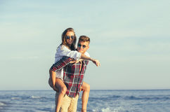 Happy couple in love on beach summer vacations. Joyful girl piggybacking on young boyfriend having fun Stock Photo