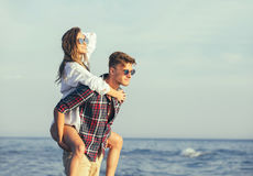 Happy couple in love on beach summer vacations. Joyful girl piggybacking on young boyfriend having fun Royalty Free Stock Photo