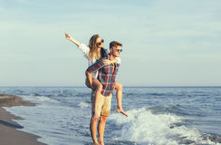 Happy couple in love on beach summer vacations. Joyful girl piggybacking on young boyfriend having fun Royalty Free Stock Image