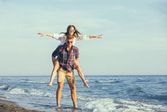 Happy couple in love on beach summer vacations. Joyful girl piggybacking on young boyfriend having fun Royalty Free Stock Photos