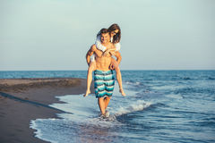 Happy couple in love on beach summer vacations. Joyful girl piggybacking on young boyfriend having fun Royalty Free Stock Photography