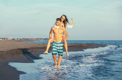 Happy couple in love on beach summer vacations. Joyful girl piggybacking on young boyfriend having fun Stock Photos