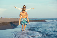 Happy couple in love on beach summer vacations. Joyful girl piggybacking on young boyfriend having fun Stock Photography