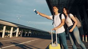 Happy couple in love catching a taxi standing with luggage near the airport, traveling. The concept of rest, vacations. Advertising taxi service stock footage