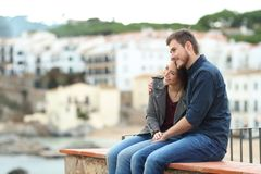 Couple in love contemplating views on a ledge. Happy couple in love contemplating views on a ledge with a town in the bakground stock image