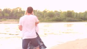 Couple in love on beach. Happy couple in love in date on beach in spring / summer near river / water. Female / woman pull male / man and running along beach stock video