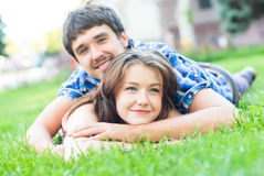 Happy couple in love embracing lying outdoors Stock Photo