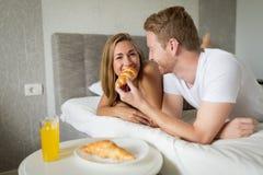 Couple enjoying breakfast in bed. Happy couple in love enjoying breakfast in bed Stock Image